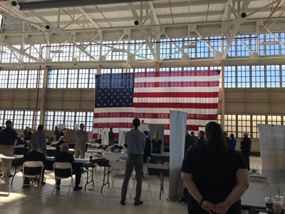 A photo from the naval air station hiring event, showing people standing at booths in a naval hangar.